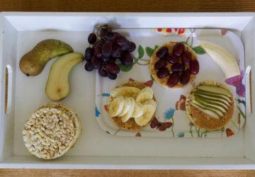 Frukostbricka med majskakor, jordnötssmör och frukt