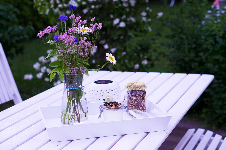Frukost ute i trädgården - fil med granola och blåbär