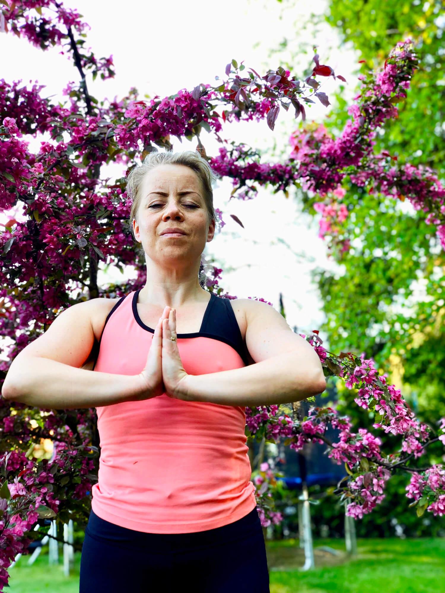 Yoga under purpurapel i trädgården